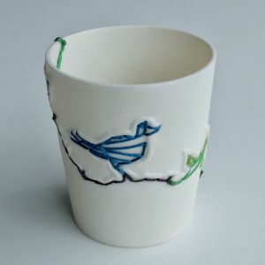 Handmade small white porcelain vessel featuring blue and green stitched birds. Decorative item.