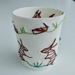 Handmade small white unglazed porcelain vessel featuring brown and green stitched low relief bunnies. Decorative item.