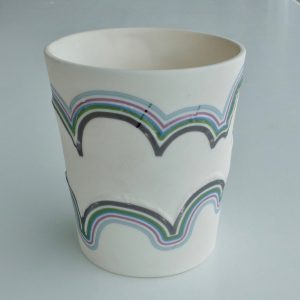 Handmade small white porcelain vessel featuring low relief clouds and multi-coloured stripes. Decorative item.