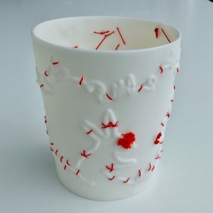 High Fired and unglazed porcelain beaker with hand stitching in silk. Please note this is a decorative object, not for use. Porcelain is delicate and strong giving fine detail and some translucency