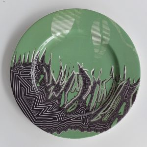 White Bone china charger with green and black abstract surface pattern